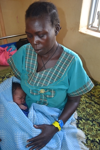 Night cuddles her new baby at Padibe Health Centre IV post-natal ward in Lamwo.