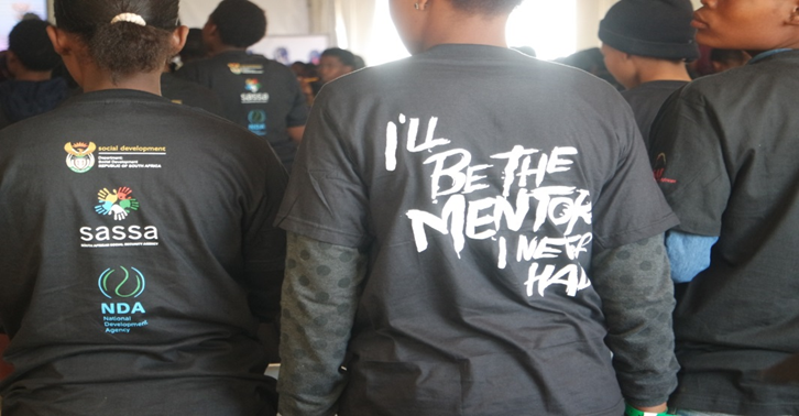 "A young girl at the assembly wearing ""I'll be the mentor I never had"" t-shirt."